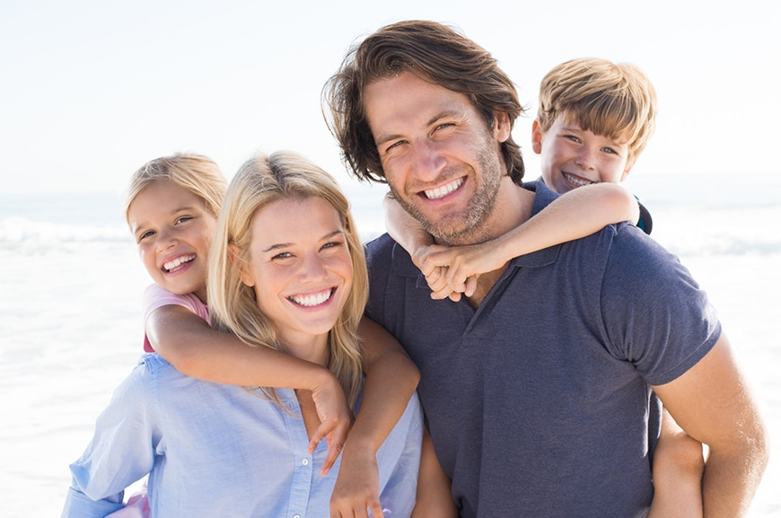Portrait of happy family looking at camera at beach.