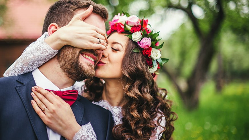 A young newly-wed couple embraces outside in nature. The bride holding her hand over the grooms eyes while he smiles in surprise. Did you know that smiling predicts your marriage, well-being, and longevity?