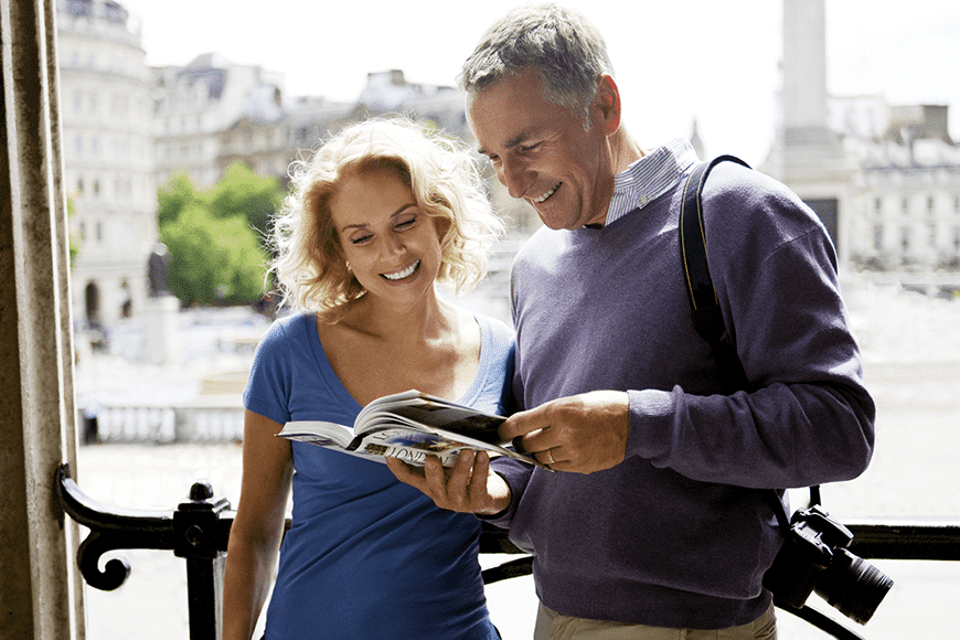 A middle-aged couple standing outside during a vacation, looking at a guidebook