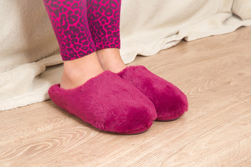 A set of fuzzy hot pink slippers resting on a young woman's feet. If you teeth feel this way, it's time to make an appointment with James, B Polley, DDS