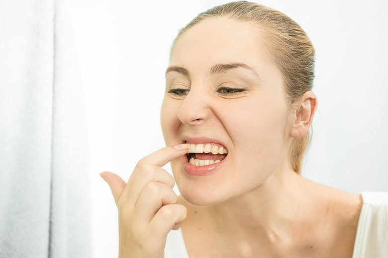 Female standing in front of a mirror with food stuck in her teeth. Is this a sign of needing orthodontics?