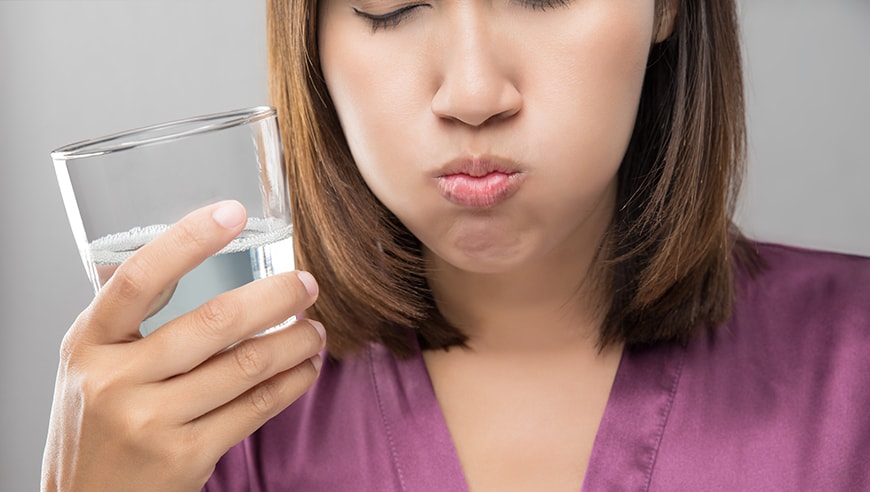 Young female using Peroxide Mouthwash while swishing it around in her mouth. While there are a lot of benefits, there is a better alternative with CariFree