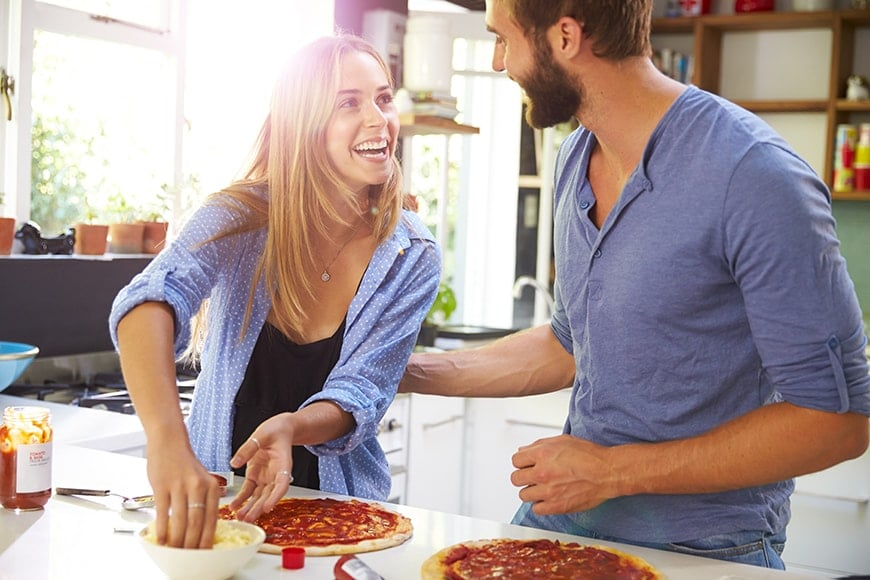 A young couple making pizza at home together. It's important to watch your diet as diabetes and gum disease have a reciprocal relationship. People with diabetes, especially those with Type 2, are at a higher risk of gum disease, and those with gum disease have a harder time controlling their blood sugar, even more a reason to contact James B Polley, DDS, Summerlin dentist.