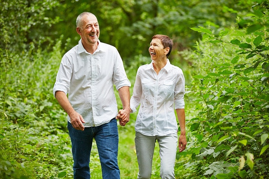 Older couple holds hands while walking and laughing in the forest. It's important to focus on your health, especially your gums. It is the leading cause of tooth loss among adults in the US, but its effects spread far beyond your teeth. That's why it's important to visit a Summerlin dentist like Dr. James B Polley.