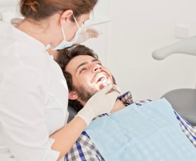 A man rests in a dental chair during a checkup and routine hygiene appointment so he can help reduce his risk for cavities. Preventive dental care is the best way to fight dental problems.