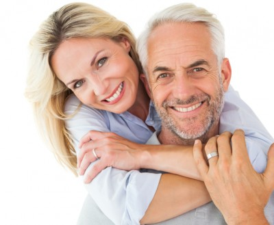 A happy couple shows off their smiles with the help of maintaining good oral health and routine checkups.
