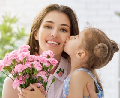 A happy mother receives a kiss on the cheek from her daughter while holding flowers. To accomplish the look you deserve look at having a smile makeover.