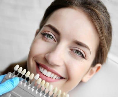 A woman rests in a chair with a dentist comparing teeth coloring. Professional teeth whitening can give you a bright smile.