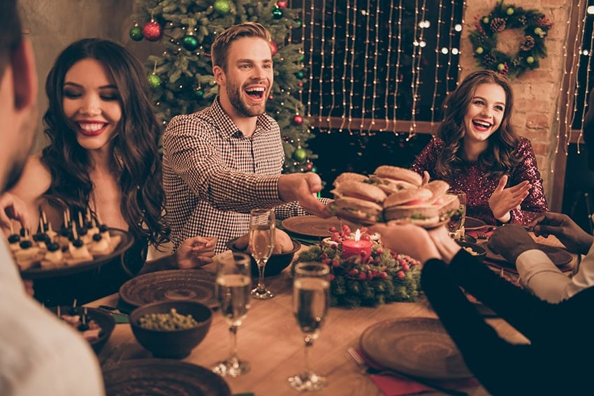 An excited group of friends enjoy the holidays together. Especially during this busy time of year it's important to remember tips of keeping your breath fresh!