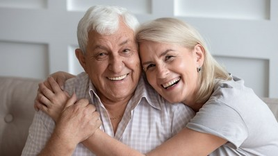 Happy mature couple in love seated on couch hugging