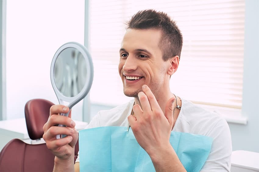 Man proud of his white smile looks in the mirror at his dentist office
