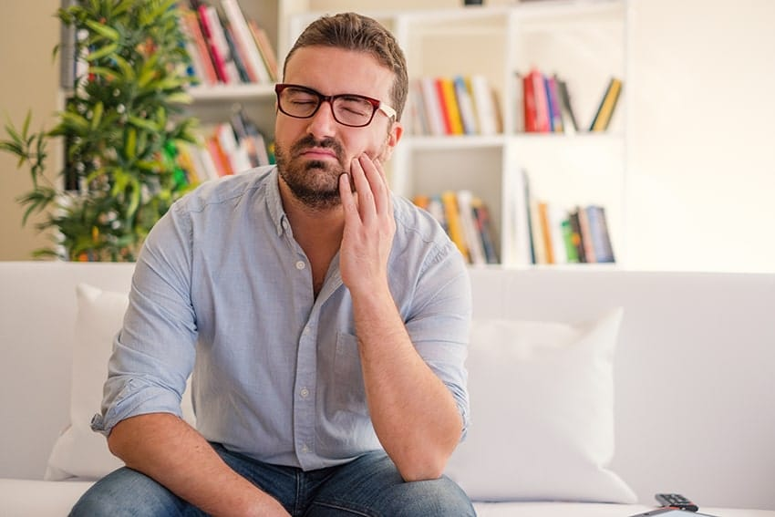 man with a toothache sits on his couch