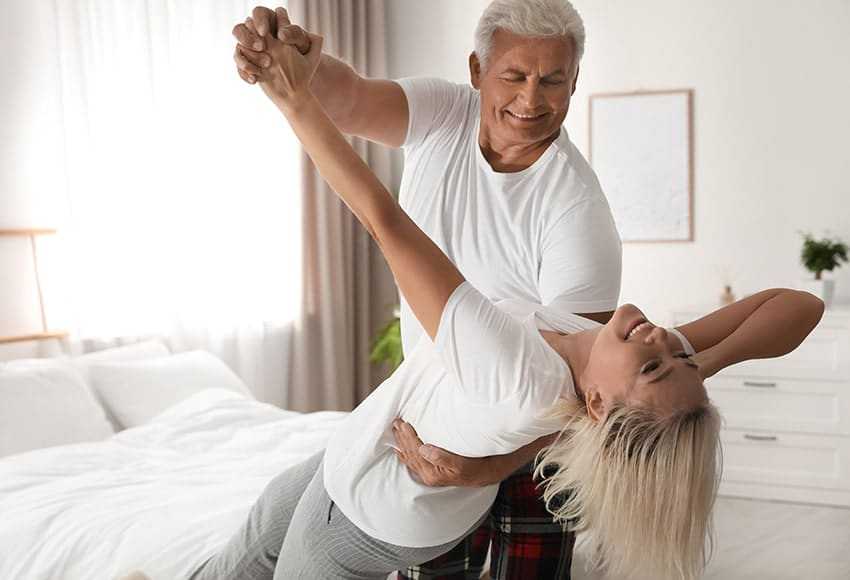 Energetic happy mature couple dances in their bedroom