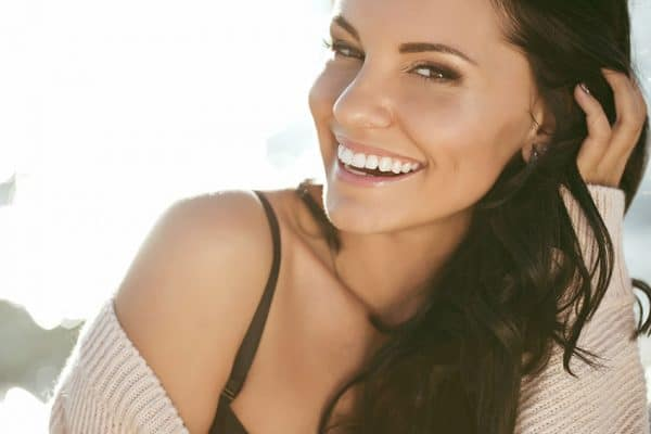 Young brunette woman enjoys time outside with her gorgeous smile