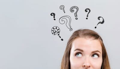 young woman with animated question marks above her head, thinking about dental implants