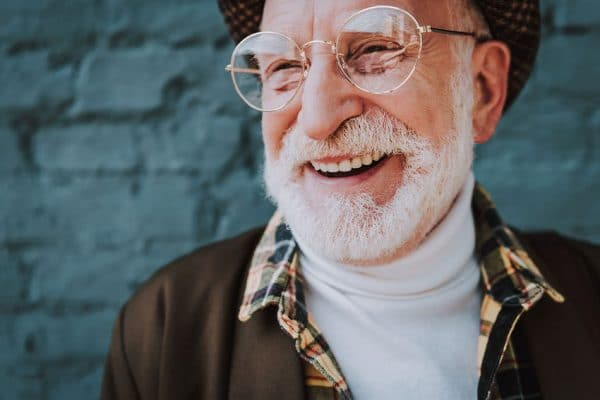 happy older man with large glasses shows off his smile