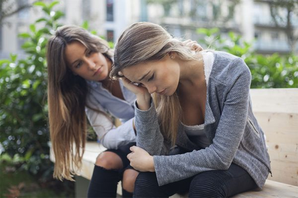 Woman consoling her friend while sitting outside on a bench