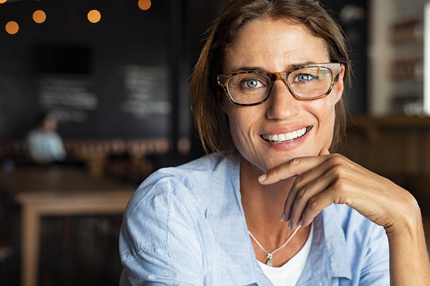 mature woman with large glasses showing off her amazing smile