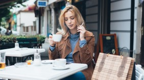 Beautiful blond woman sitting alone in cafeteria, smoking a ciga