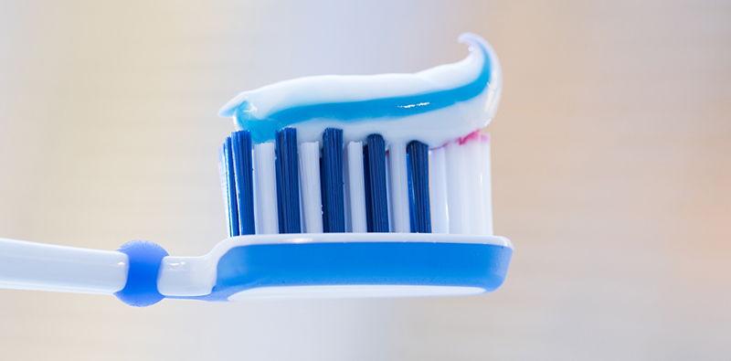 Toothbrush with toothpaste on blurred background