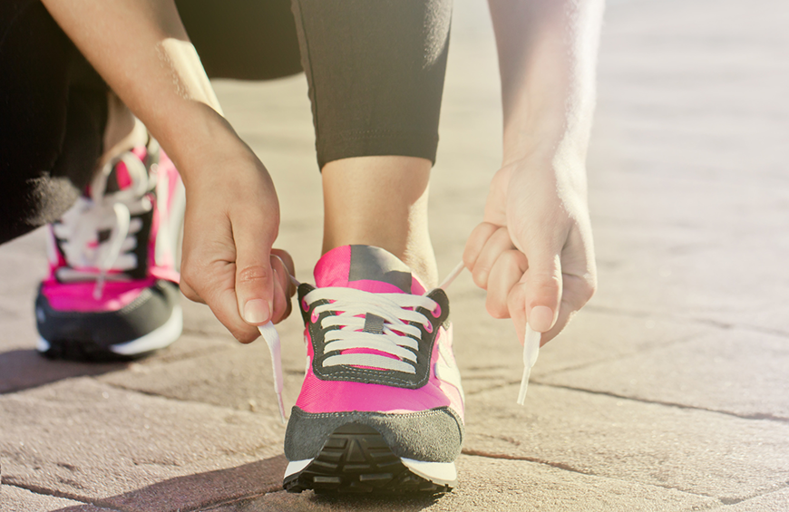 A woman smiling while tying her shoes before a run