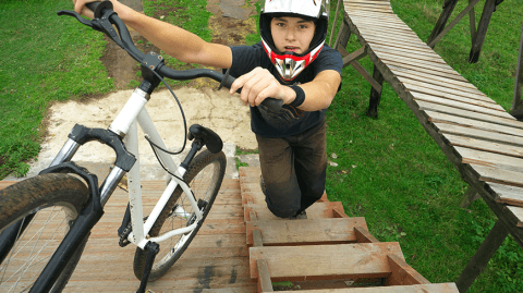 young boy go up to the ramp with his BMX Bike